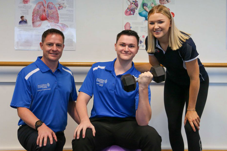 Young man sitting on a purple fit ball doing a bicep curl, with a young woman to one side, and a man to the other