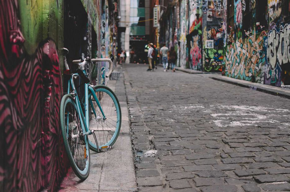 Green bicycle in the foreground of a photo of the graffiti art space, Hosier Lane